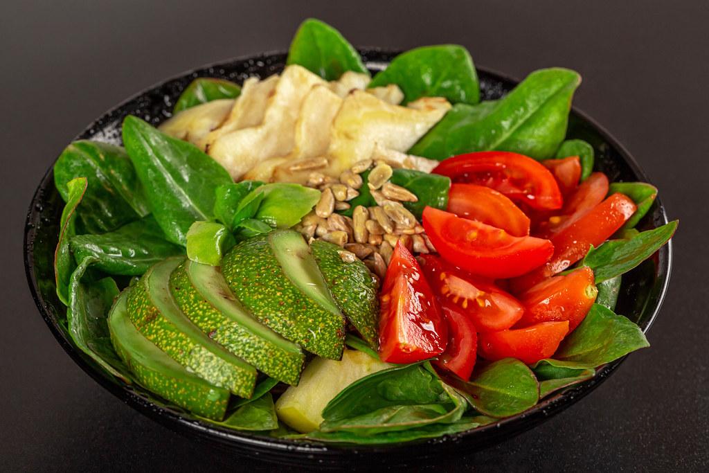 Healthy vegetable salad with sunflower seeds on dark background