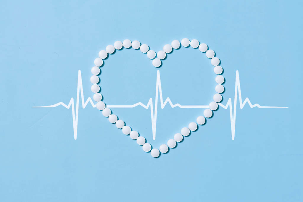 Heart shape made of medical pills and cardiogram