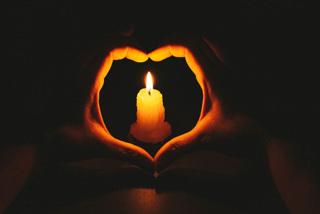 Heart-shaped hands and flame candle in darkness