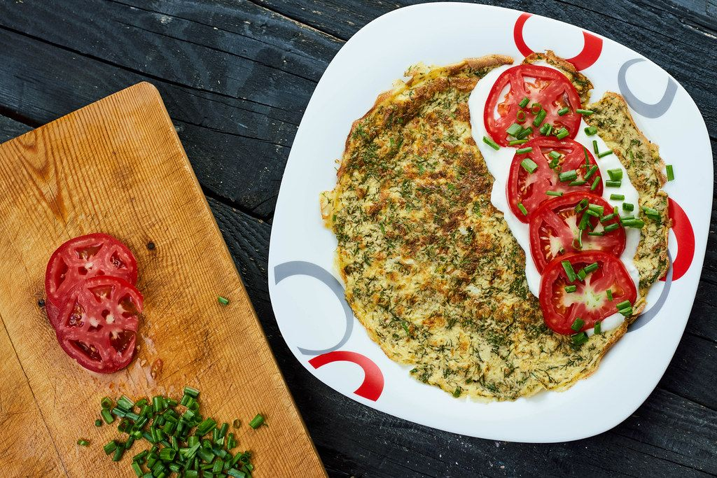 Herbs based omelet and and tomato slices with sour cream