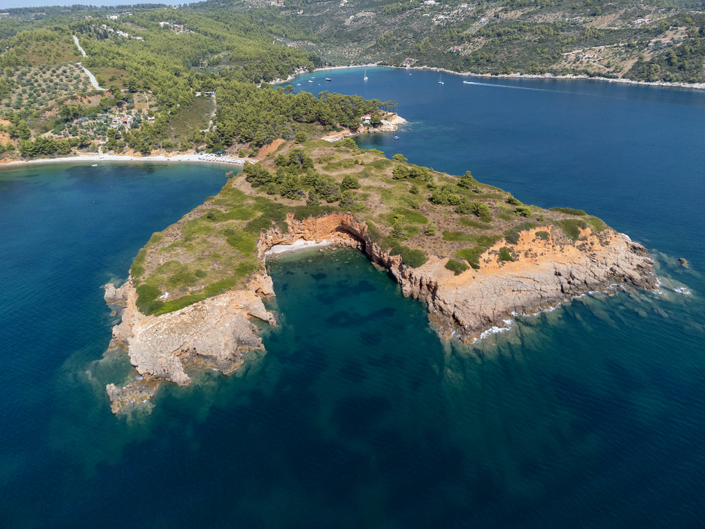 Hidden beach with red cliffs formed by the headland of Kokkinokastro seen from the sea with a drone