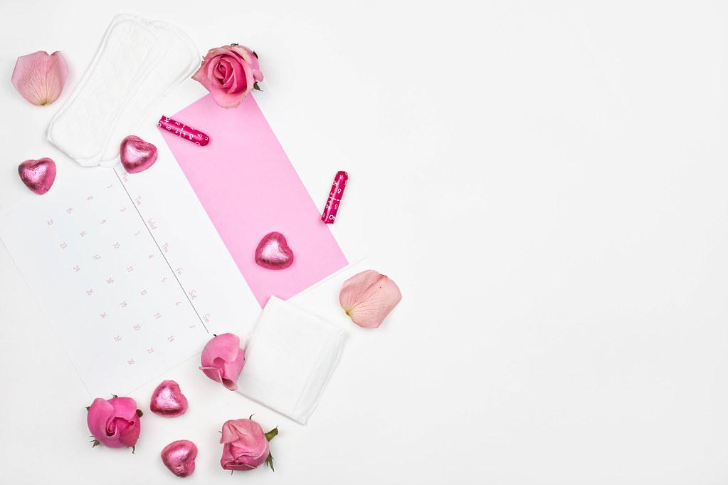 Hintergrund mit Platz für Text, Menstruation-Kalender, Schokoherzen, Rosen, Slipeinlagen und Tampons
