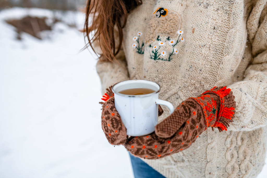 Holding Hot Tea Outdoors With Warm Mittens