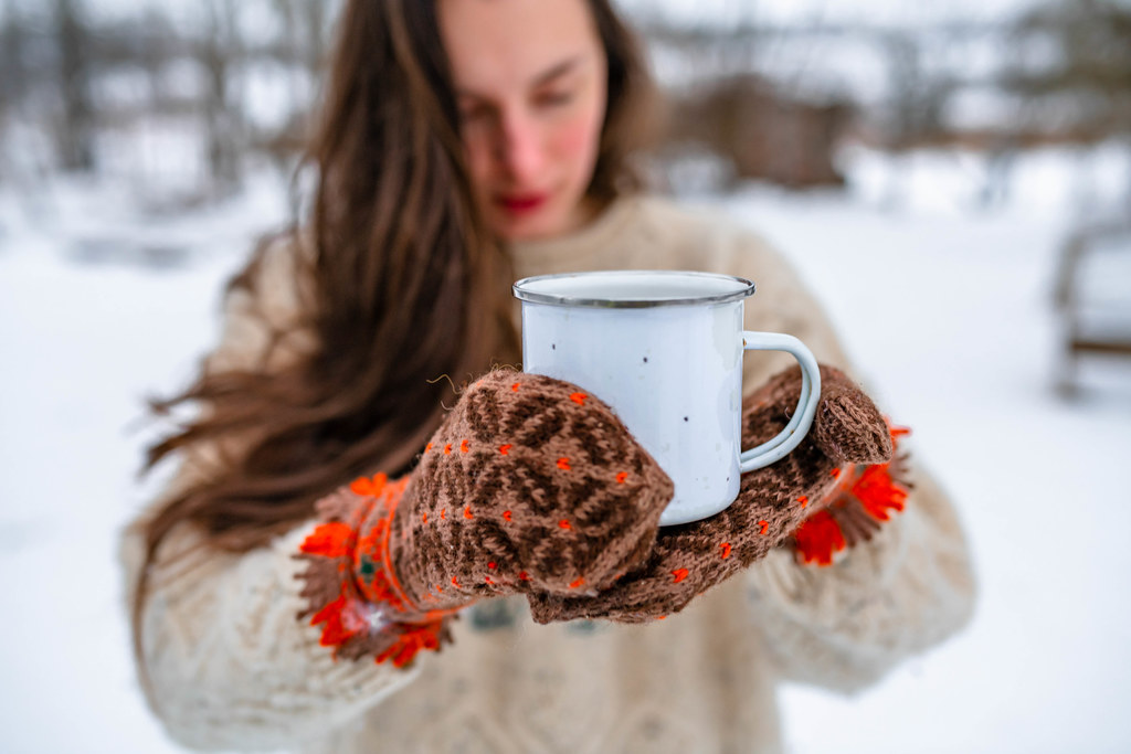 Holding Tea In Metal Cup With Wool Mittens