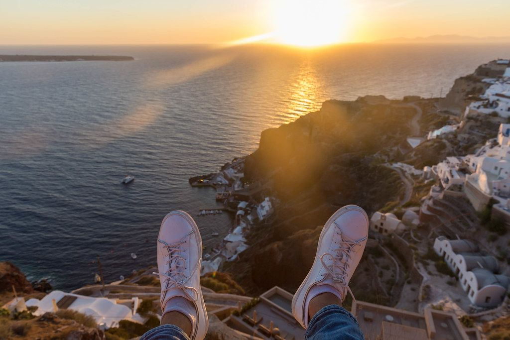 Holiday feeling in Greece: feet of a man watching the sunset and enjoying the views of Santorini