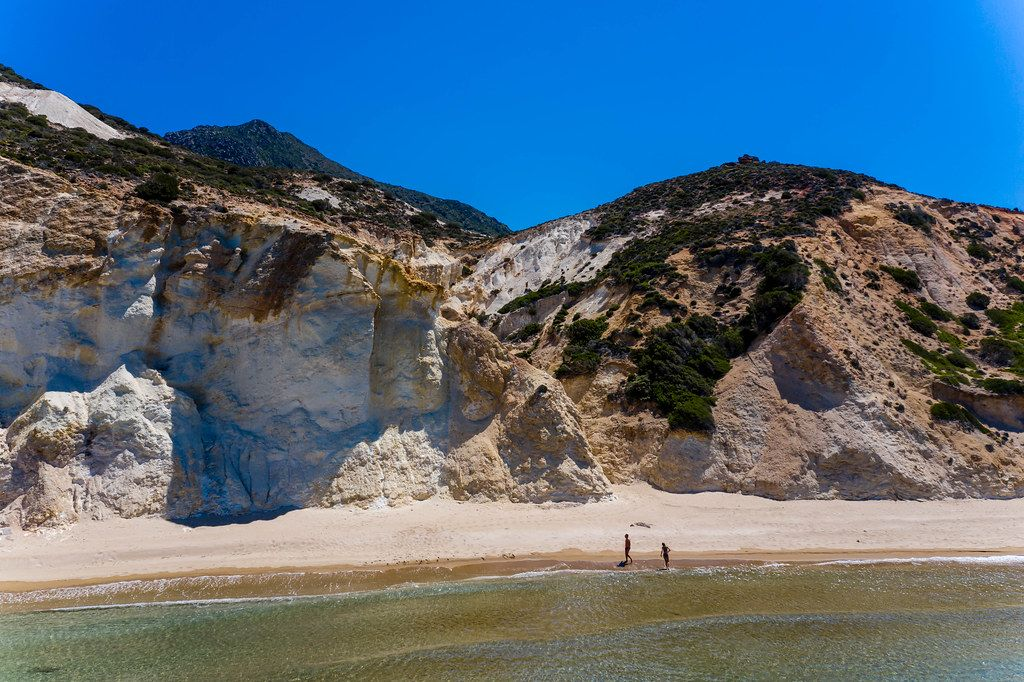 Holiday in Greece: almost deserted beach with just two people walking in the sun on the island of Milos