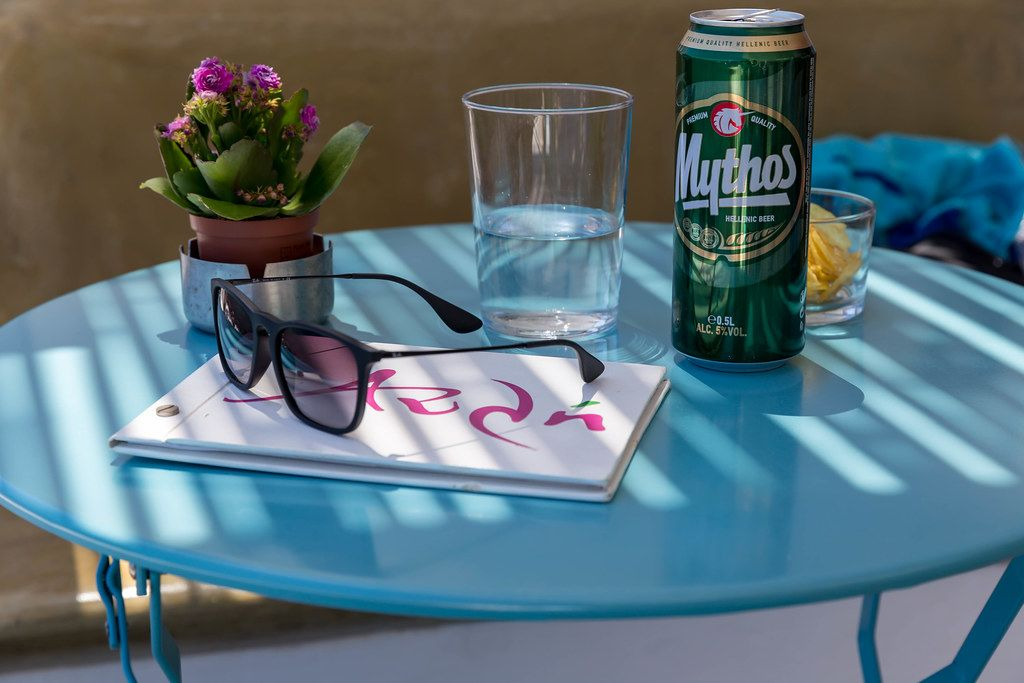 Holiday in Greece: sunglasses, flowers, a can of Mythos beer, water and menu on a blue table