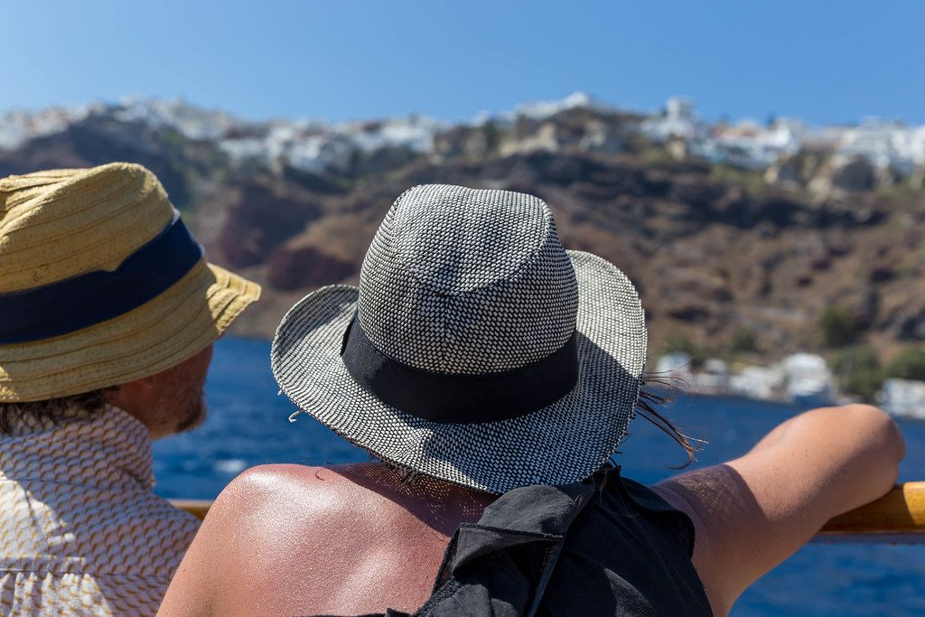 Holiday in Greece: tourists wear hats protecting them from the scorching sun, seen from the back