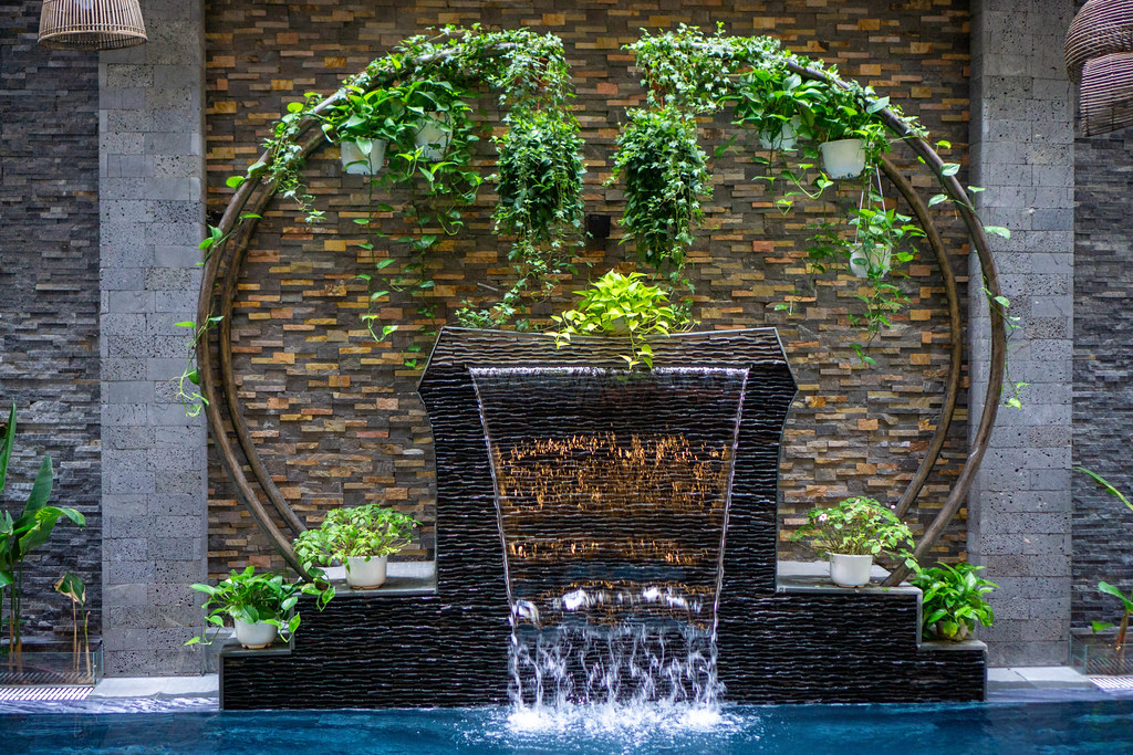 Holzbogen mit Hängepflanzen um einen künstlichen Wasserfall an einem Pool vor einer modernen Ziegel Wand in einem Hotel