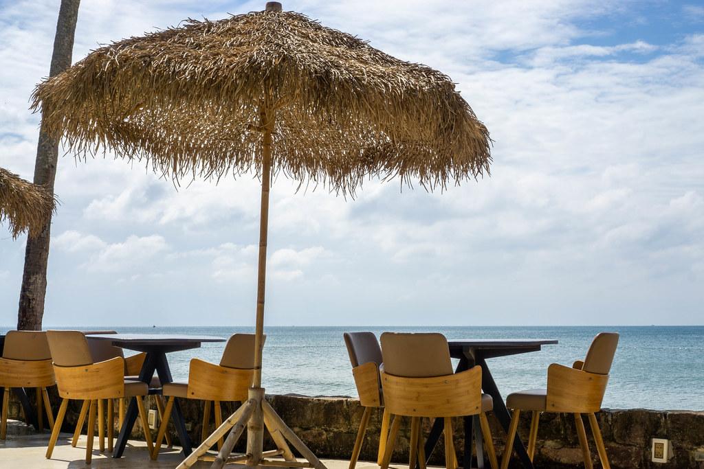 Holztische, Holzstühle und Sonnenschirm aus Palmenblättern bei einer Strandbar mit Aussicht auf das Meer in Phu Quoc, Vietnam