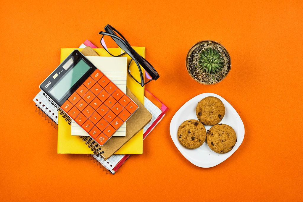 Home office. Notepad, calculator, cactus and cookies on orange background