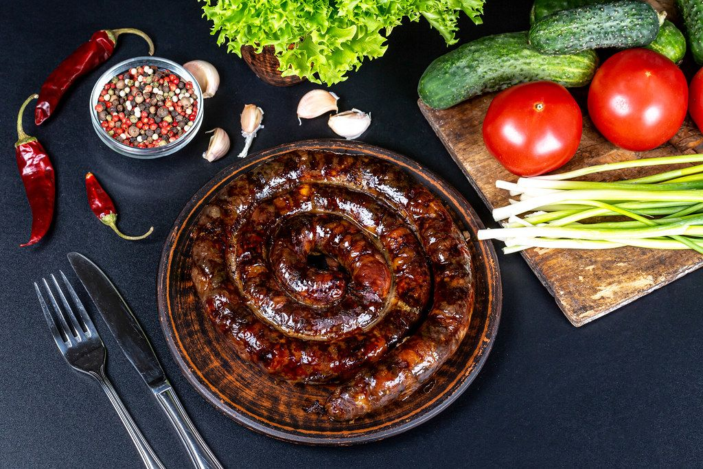 Homemade sausage with spices and vegetables on black background