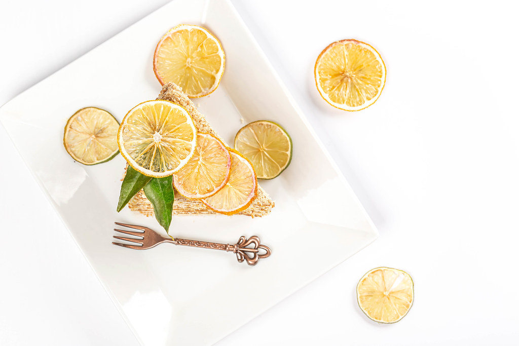 Honey cake with condensed milk on a white plate with a fork and dried lemon and lime, top view