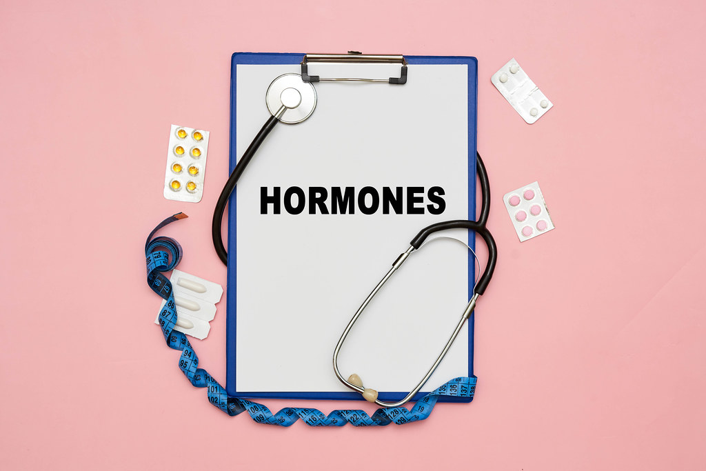 Hormones word on white paper card with medical equipments and pills