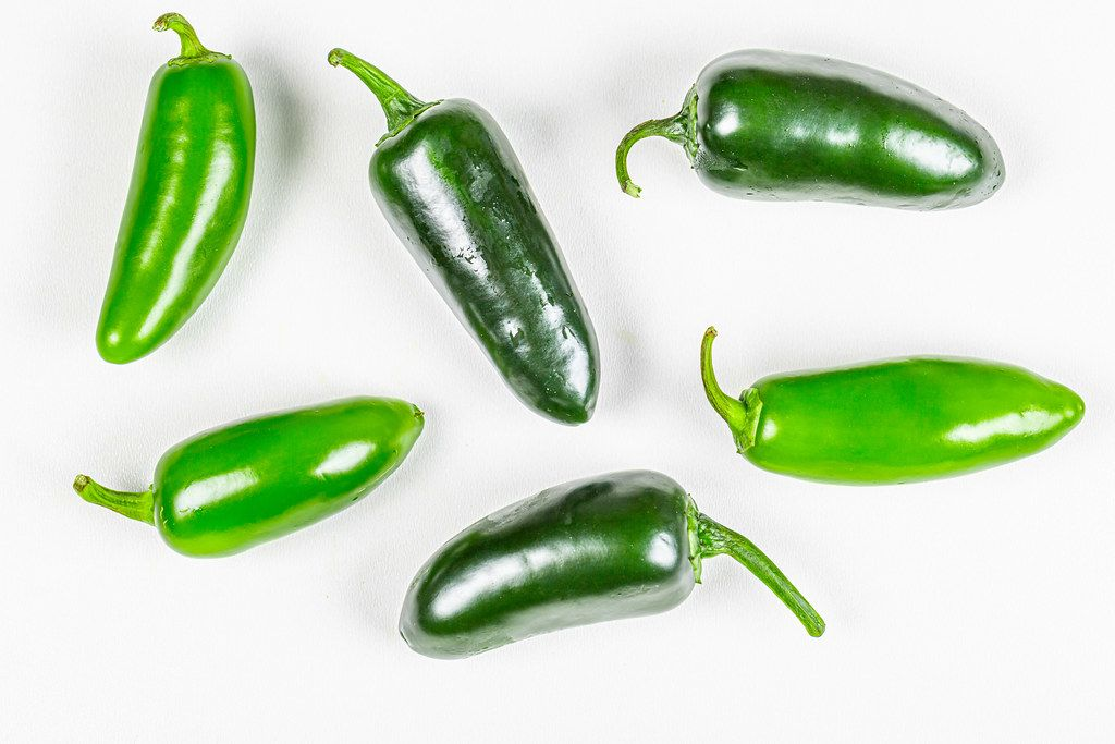 Hot green chili jalapeno on a white background, top view