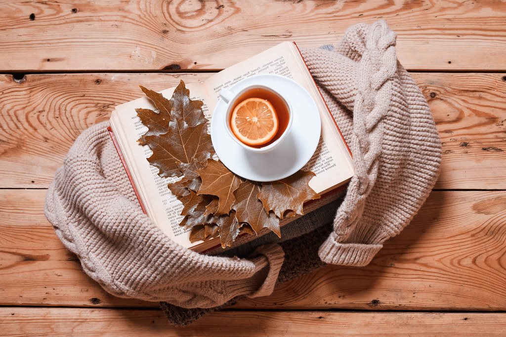 Hot lemon tea, book and autumn leaves with knitted sweater on rustic wood