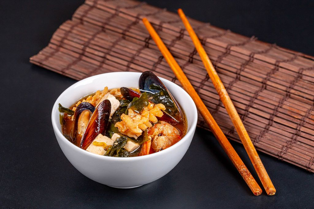 Hot miso soup with seafood in white bowl on dark background