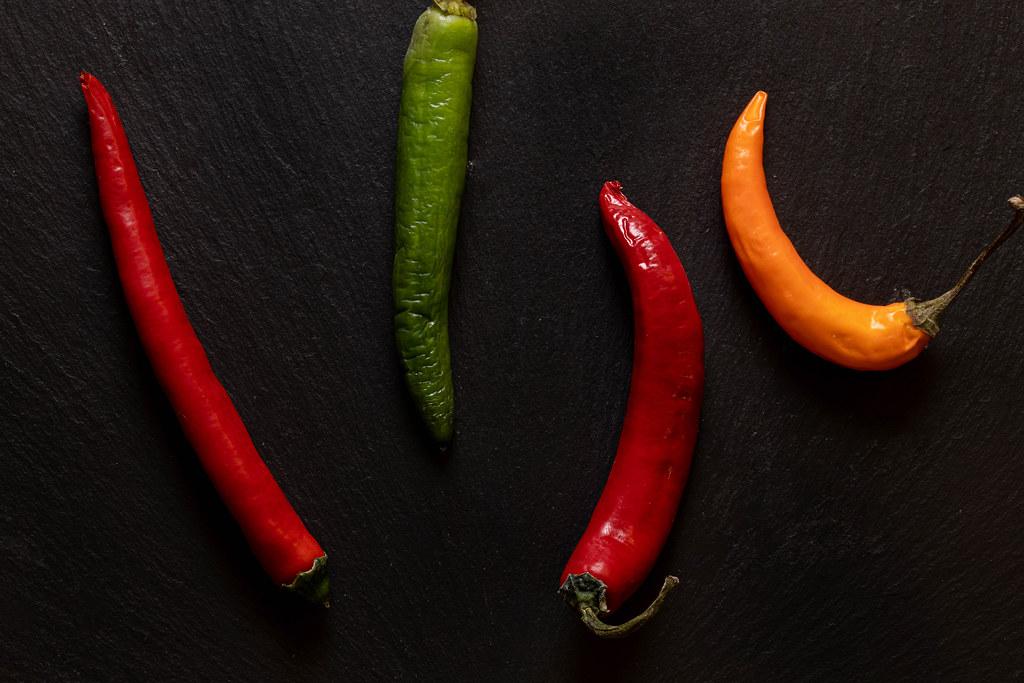 Hot Paprika above black background concept