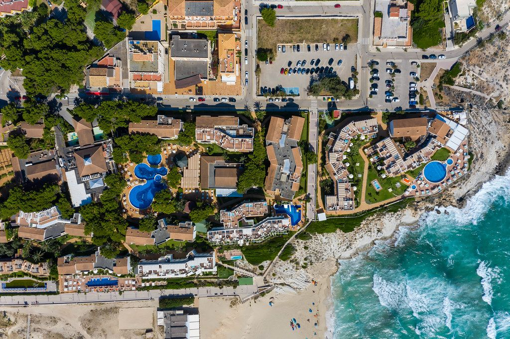 Hotels and apartment complexes with pools for holidays in Majorca. Overhead shot, Cala Mesquida