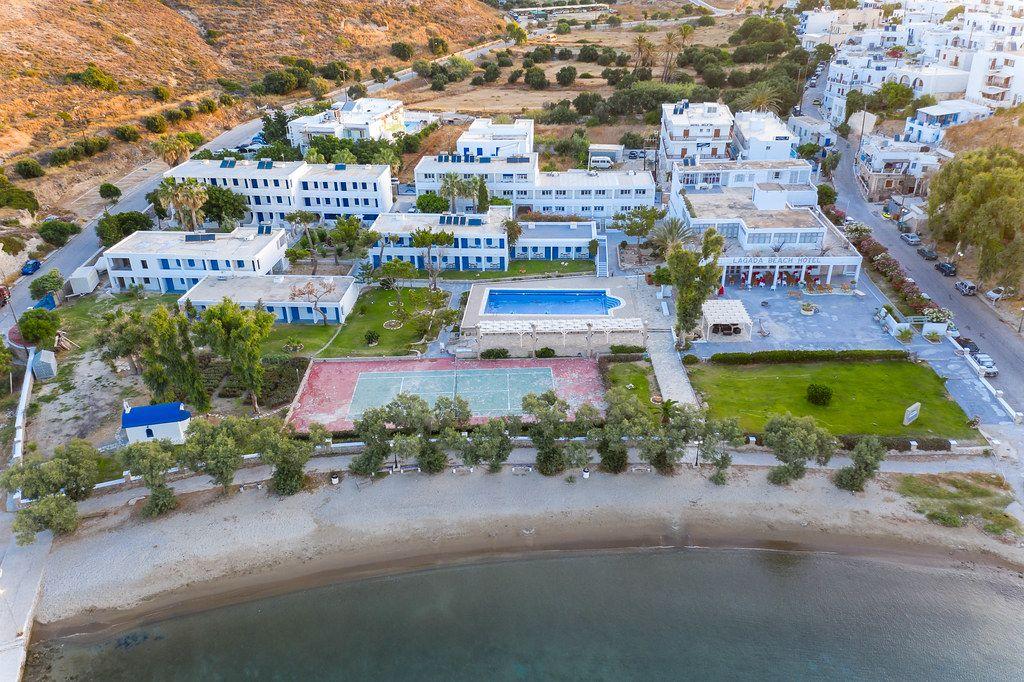 Hotels, Schwimmbad, Tennisplatz und Strand. Luftaufnahme von Adamantas, Milos, Griechenland