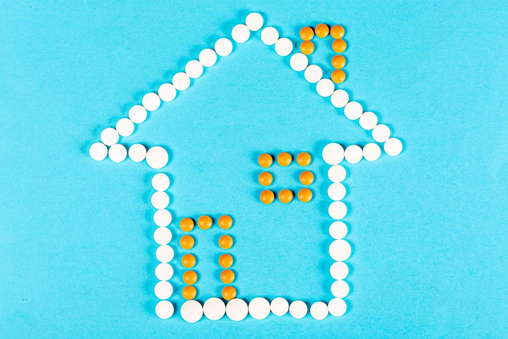 House made of pills on a blue background. The concept of being treated at home