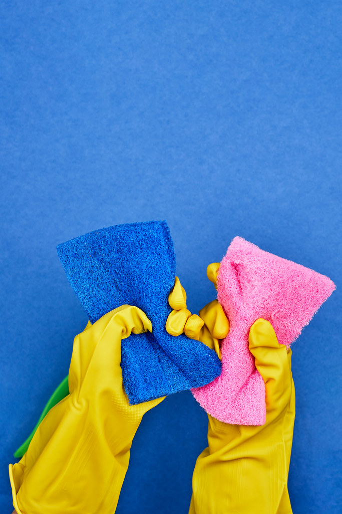 Housemaid in yellow rubber gloves holds cleaning sponges