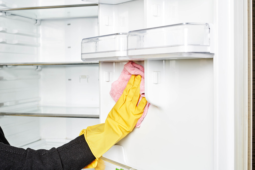 Housewife hands in rubber protective glove with microfiber cloth cleaning a fridge
