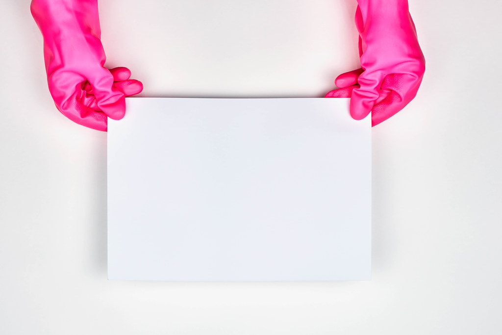 Housewife in red protective gloves hold a blank paper card with copy space