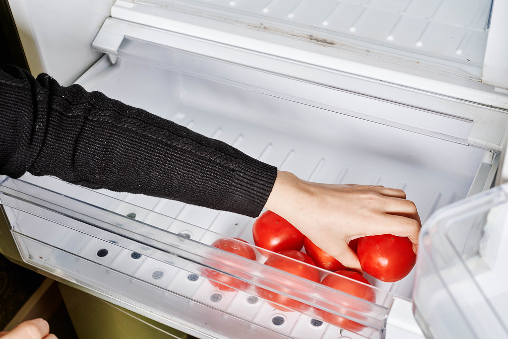 Housewife putting fresh tomatoes into the fridge