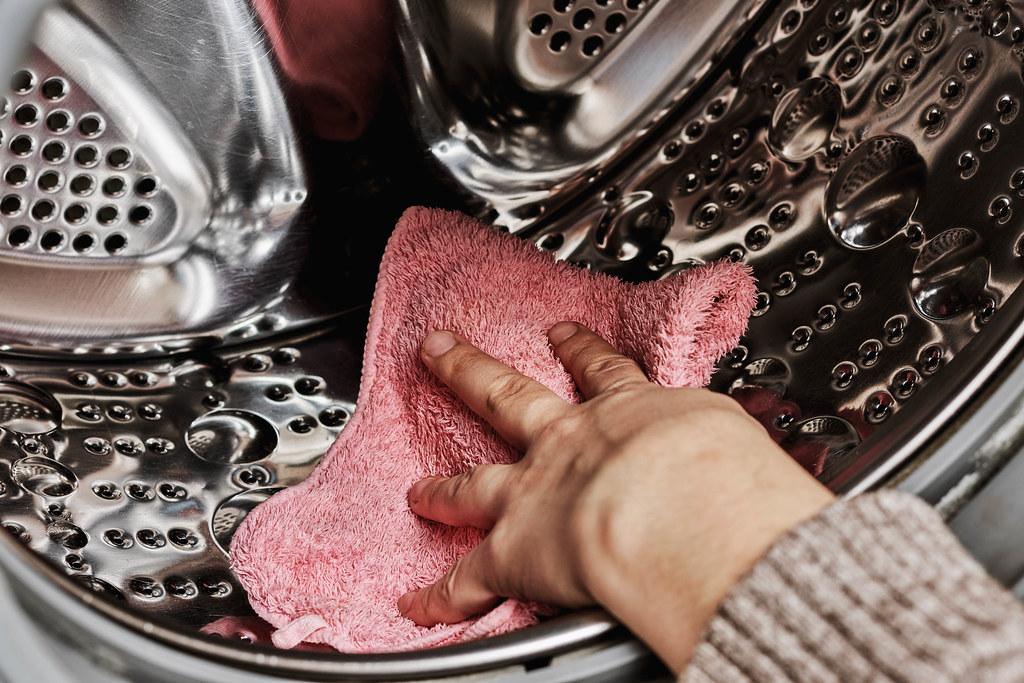 Housewife wiping washing machine drum