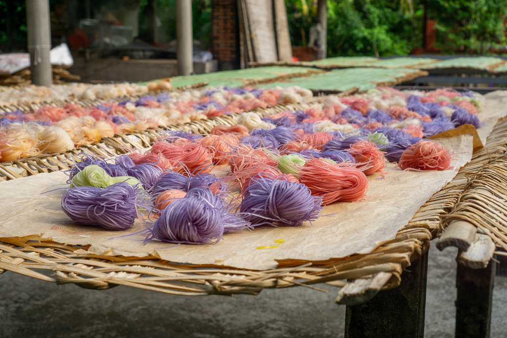 Hu Tieu Tapioka Nudeln mit verschiedenen Zutaten wie Süßkartoffeln oder blauer Schamblume trocknen in der Sonne in einer lokalen Nudelfabrik in Can Tho, Vietnam