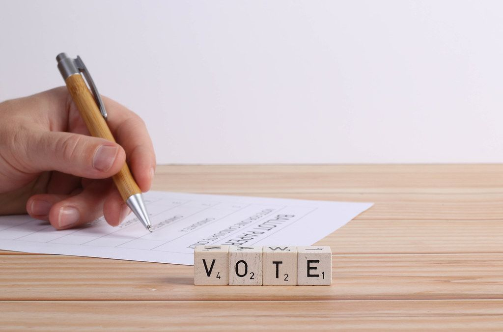 Human hand with ballot paper and vote text
