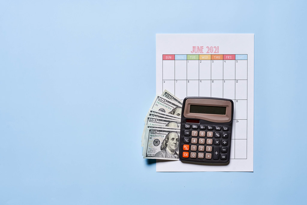 Hundred US dollar bills and calculator on calendar