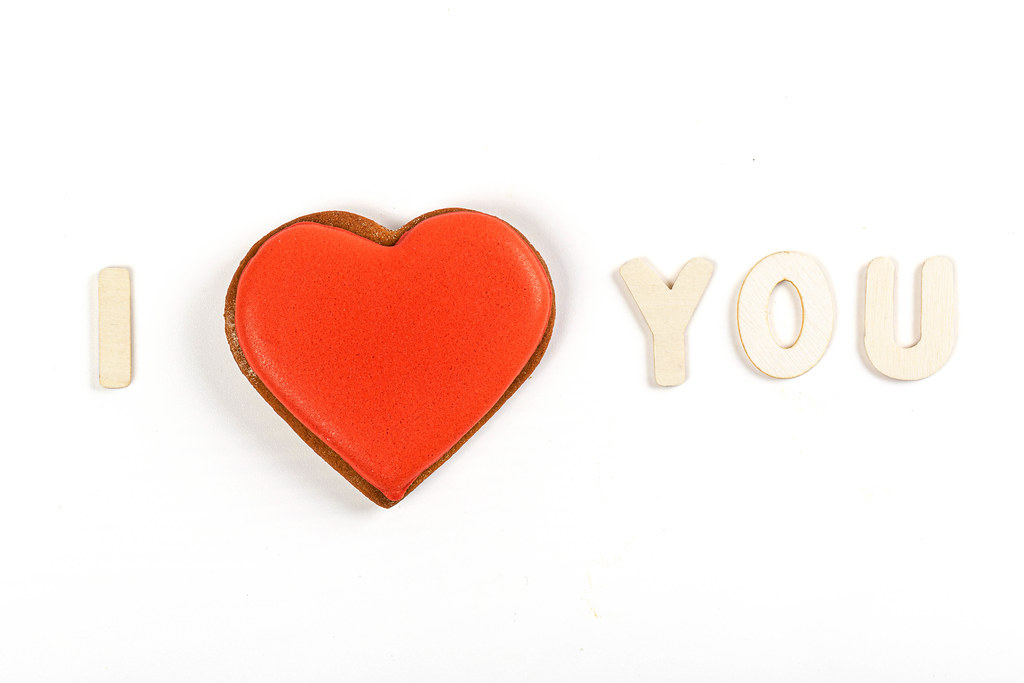 I love you - made of wooden letters and red gingerbread heart on white