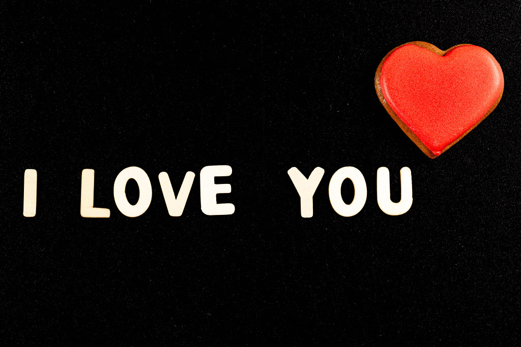 I love you - made of wooden letters on a black background with a gingerbread heart