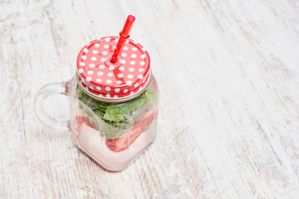 Iced summer drink cocktail with strawberry and fresh mint