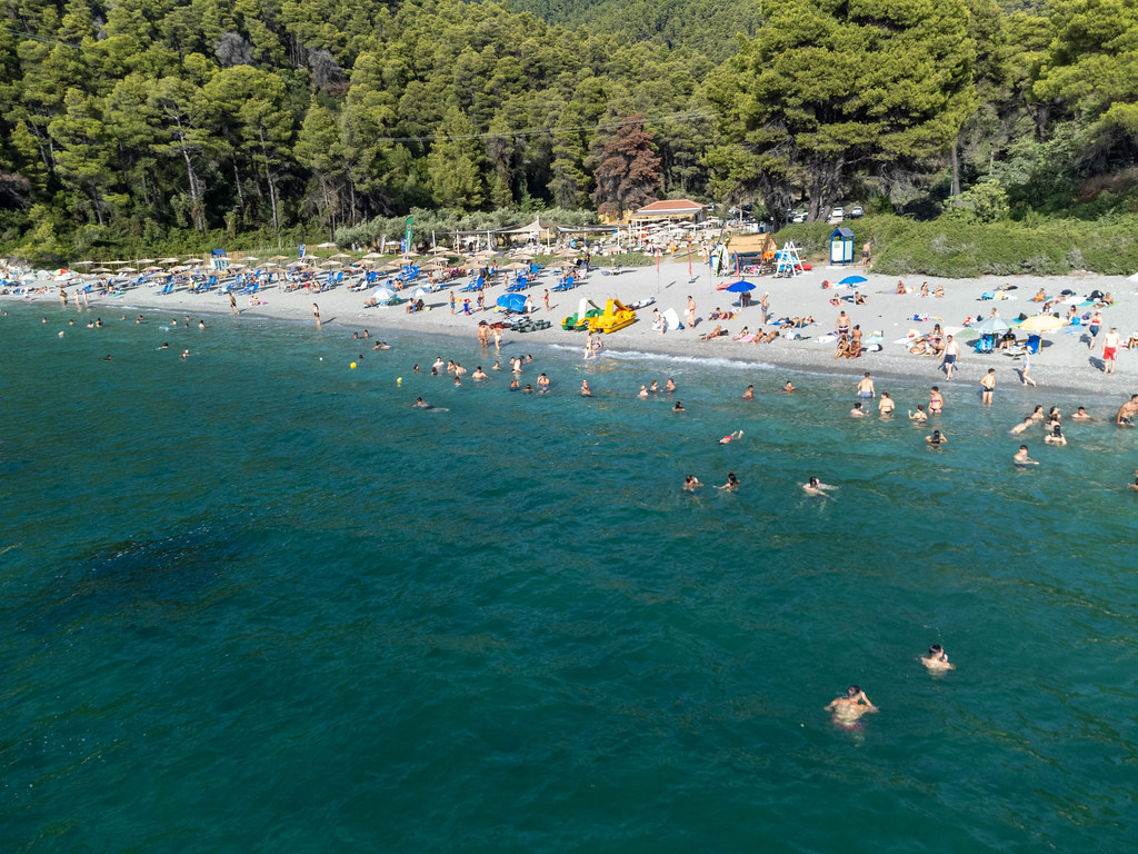 In the footsteps of Mamma Mia! movie: tourists on famous Kastani beach on Skopelos seen from the sea