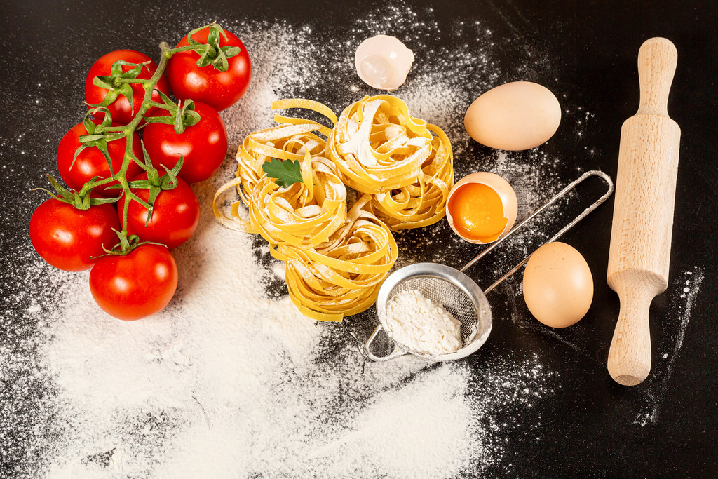 Ingredients for cooking fettuccine with raw eggs, tomato and flour