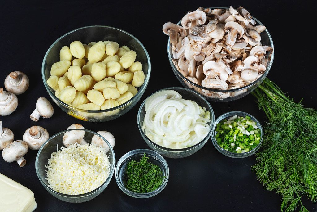 Ingredients for making potato gnocchi with mushrooms and cheese on a black background