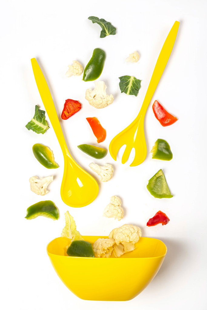 Ingredients for vegetable salad scattered on white background with yellow salad bowl, spoon and fork