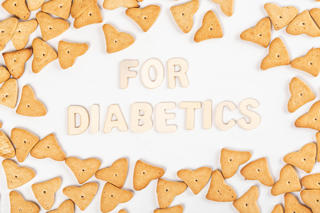 Inscription for diabetics made of wooden letters on white with cookie frame