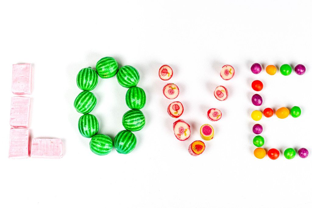 Inscription love from multi-colored sweets on a white background