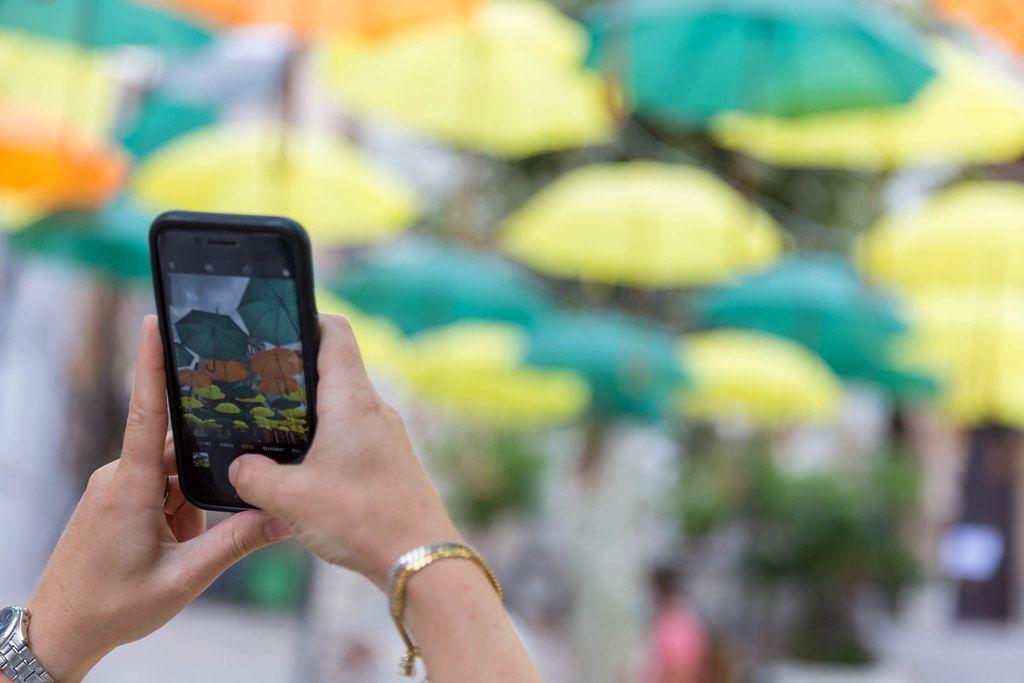 Installation in Sóller: Hände einer Frau, die mit dem iPhone Víctor Balaguers Regenschirmen fotografiert