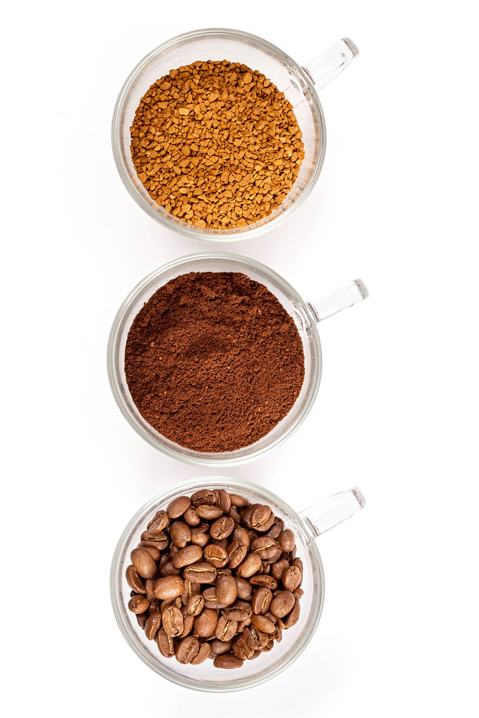 Instant, ground and coffee beans in glass cups on white, top view
