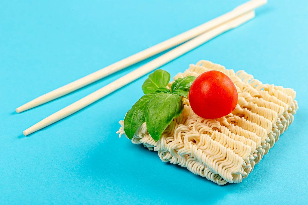 Instant noodles on blue background with chopsticks, basil and tomato