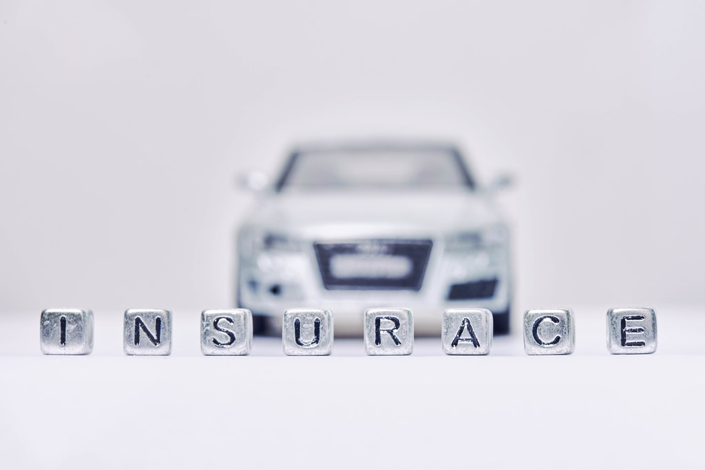 Insurance word made of miniature blocks and automobile toy