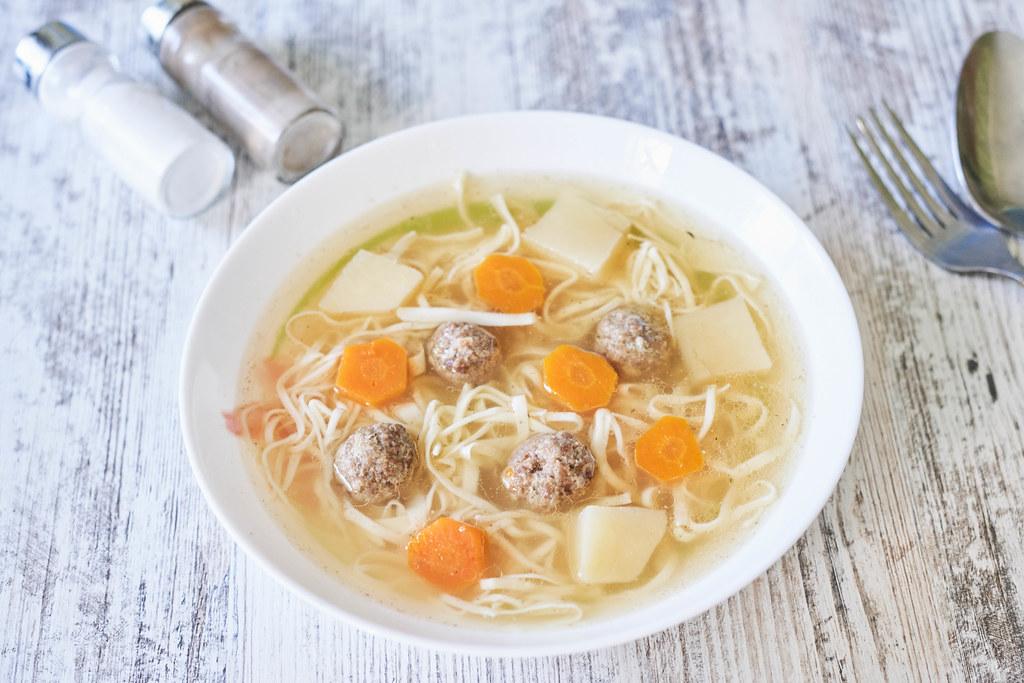 Italian meatball soup on wooden table