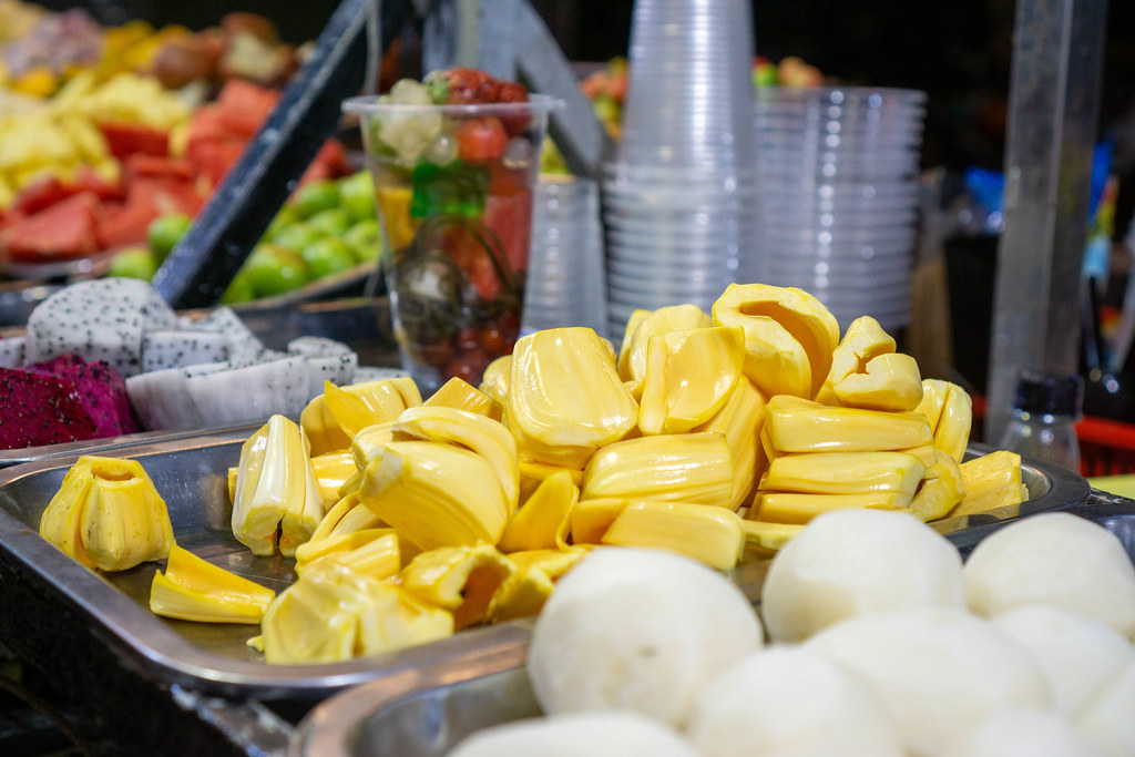 Jackfrucht, Rote und Weiße Drachenfrucht und andere Früchte mit Plastikbechern im Hintergrund bei einem Essensstand auf einem Nachtmarkt in Vietnam