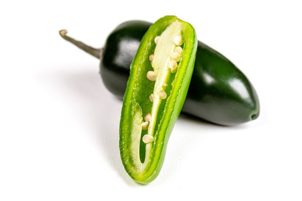 Jalapeno pepper whole and half on a white background