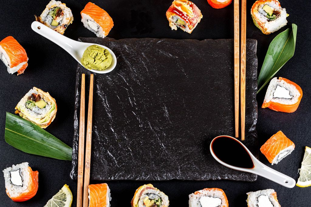 Japanese food frame with different sushi, sauces and chopsticks on black background, top view